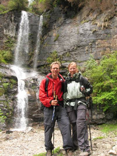 Paul and Fiona in front of a waterfall on the way to Lukla. Photo Mary Adler.