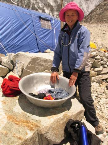 Mary washes her clothes outside the dining tent at base camp. Photo Paul Adler.