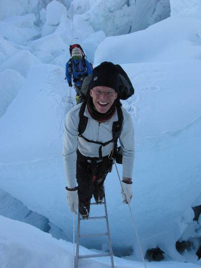 Climbing over a ladder halfway up the icefall this morning. It was so warm I had to change to my sunny clothes well before the sun hit. Check out the face mask on the Sherpa behind me. Photo Atilla Jelenko.