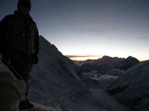 Passang Sherpa stands beside his tent on the edge of the Lhotse face at sunset a few minutes ago. Photo Paul Adler.